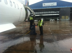 Loading my tripod into the DHC-8 hold during an OR Tambo deluge.